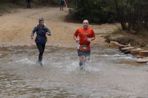 Alicia Ross and Jamie Corcoran crossing the creek in the Glow worm Half Marathon.
